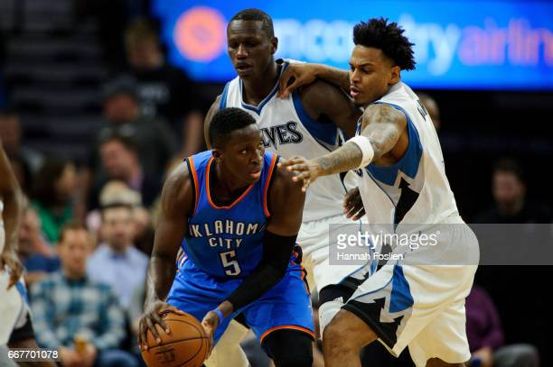 Gorgui Dieng and Brandon Rush of the Minnesota Timberwolves defends against Victor Oladipo of the Oklahoma City Thunder during the third quarter of...