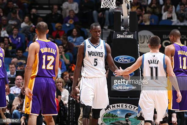 Gorgui Dieng and JJ Barea of the Minnesota Timberwolves slap hands during a game against the Los Angeles Lakers on March 28 2014 at Target Center in...