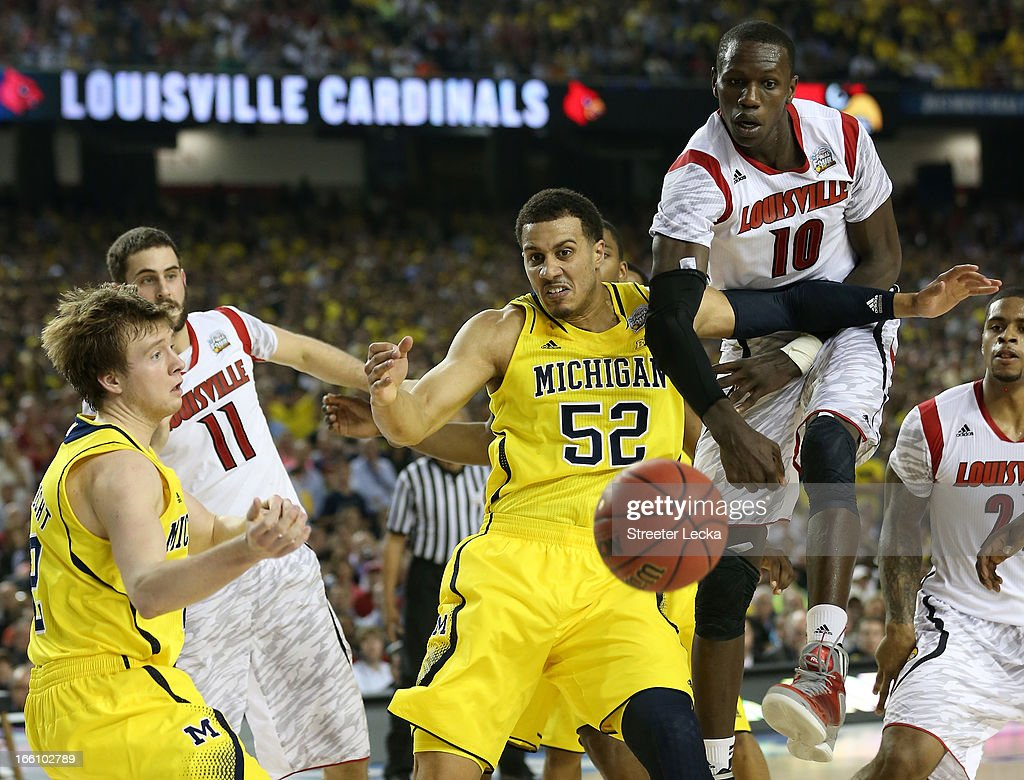 Gorgui Dieng #10 and Luke Hancock #11 of the Louisville Cardinals fight for the loose ball in the second half against Spike Albrecht #2 and Jordan Morgan #52 of the Michigan Wolverines during the 2013 NCAA Men's Final Four Championship at the Georgia Dome on April 8, 2013 in Atlanta, Georgia.