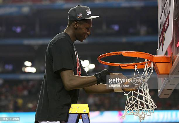 Gorgui Dieng of the Louisville Cardinals cuts down a piece of the net as Louisville celebrates their 8276 win against the Michigan Wolverines during...