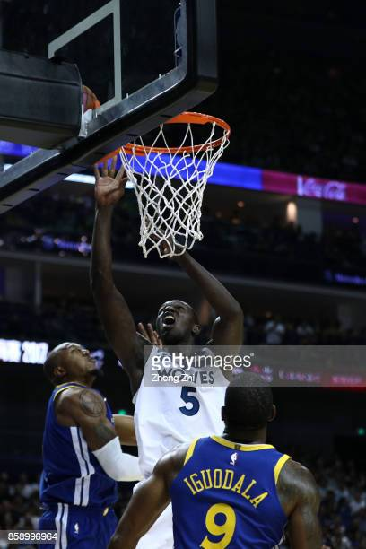 Gorgui Dieng of the Minnesota Timberwolves in action against Andre Iguodala and David West of the Golden State Warriors during the game between the...