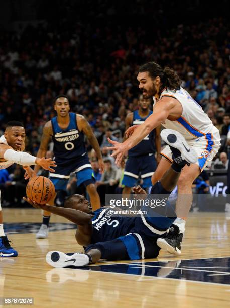 Gorgui Dieng of the Minnesota Timberwolves passes the ball away from Russell Westbrook and Steven Adams of the Oklahoma City Thunder while laying on...