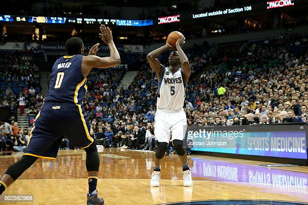 Gorgui Dieng of the Minnesota Timberwolves shoots against CJ Miles of the Indiana Pacers on December 26 2015 at Target Center in Minneapolis...