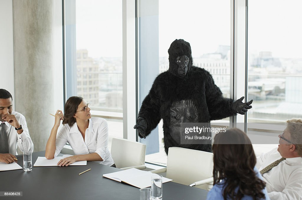 Gorilla and businesspeople having meeting in conference room