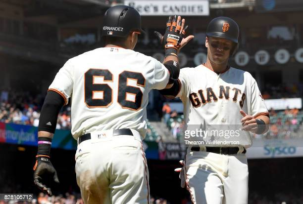 Gorkys Hernandez and Buster Posey of the San Francisco Giants celebrate after they both scored on an rbi tworun single from Nick Hundley against the...