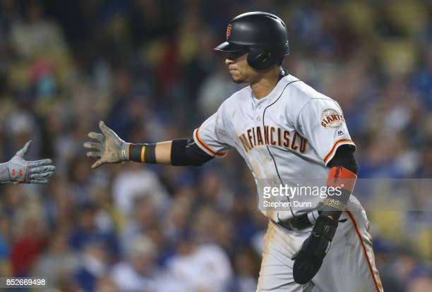 Gorkys Hernandez of the San Francisco Giants celebrates with a teammate as he returns the dugout after scoring a run in the fifth inning against the...