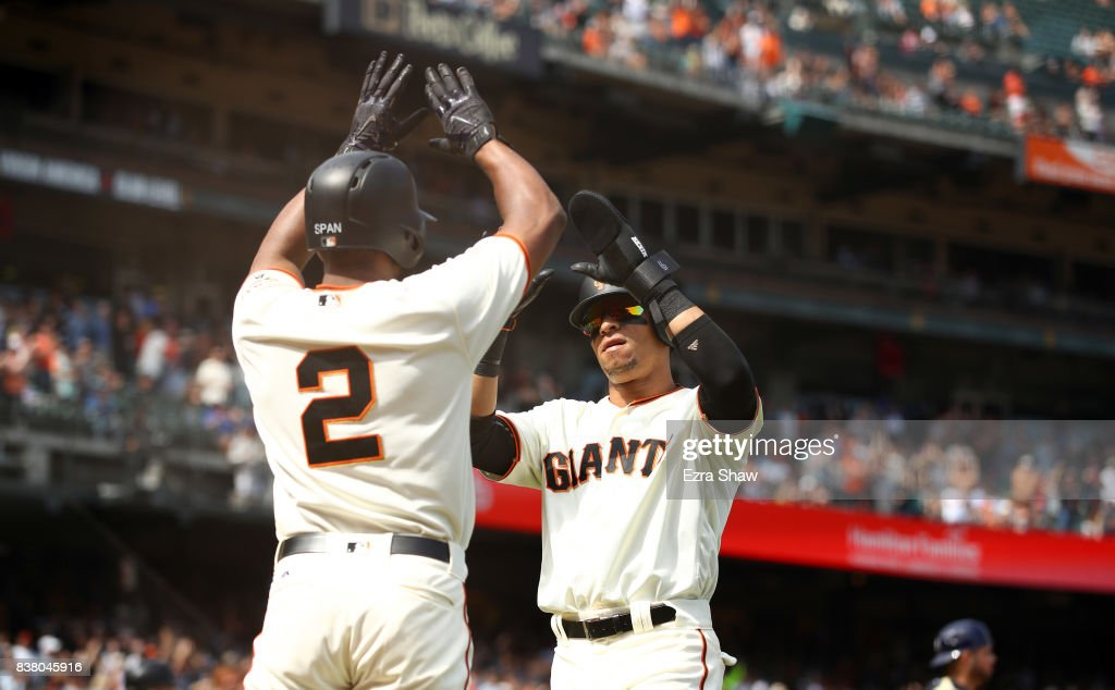 Gorkys Hernandez #66 of the San Francisco Giants is congratulated by Denard Span #2 after they both scored on a hit by Jarrett Parker #6 in the seventh inning of their game against the Milwaukee Brewers at AT&T Park on August 23, 2017 in San Francisco, California.