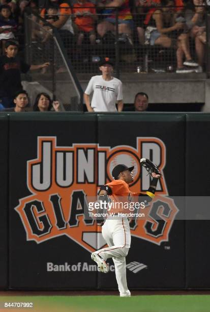 Gorkys Hernandez of the San Francisco Giants runs down this ball at the wall off the bat of Yadier Molina of the St Louis Cardinals in the top of the...