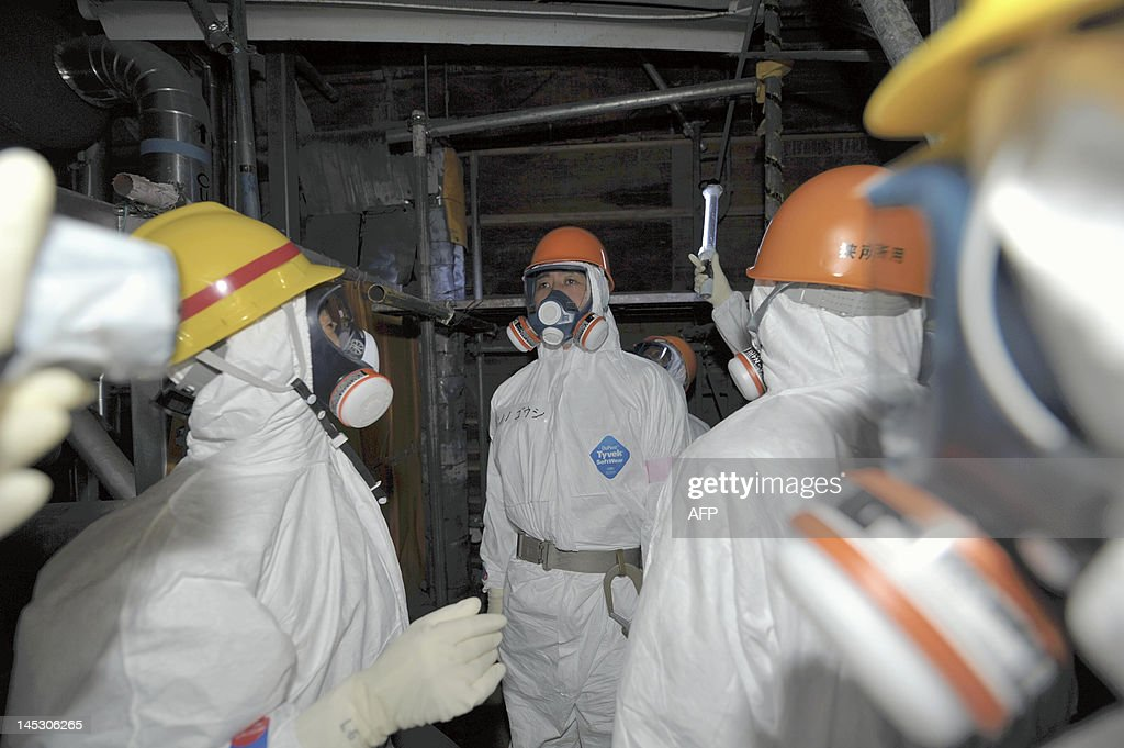 Goshi Hosono, Japan's environment minister, minister for the Restoration from and Prevention of Nuclear Accident and minister of state for the Nuclear Power Policy and Administration, (C), inspects the inside the No. 4 reactor building at Tokyo Electric Power Co.'s (Tepco) Fukushima Dai-Ichi nuclear power plant in Okuma Town, Fukushima Prefecture on May 26, 2012. Japan may look to generating 15 percent of its electricity needs from nuclear power, a minister said, as the country seeks to rebalance its energy supply after the Fukushima disaster. JAPAN OUT AFP PHOTO / Toshiaki Shimizu / JAPAN