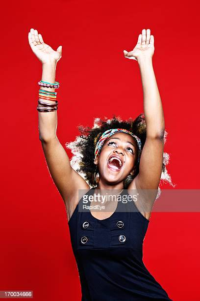 Gospel singing or praise dancing, young afro-haired woman is ecstatic