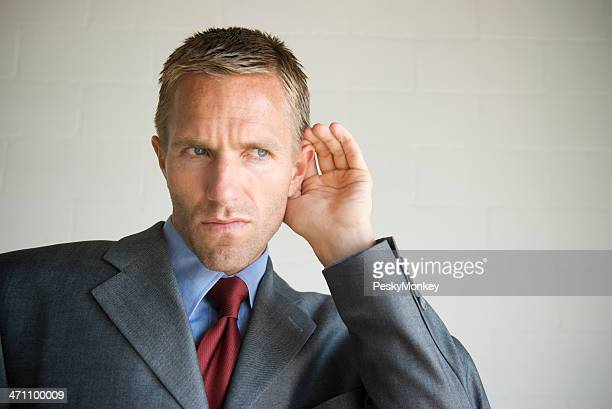 Gossip Businessman Cupping his Ear Listening to White Copy Space