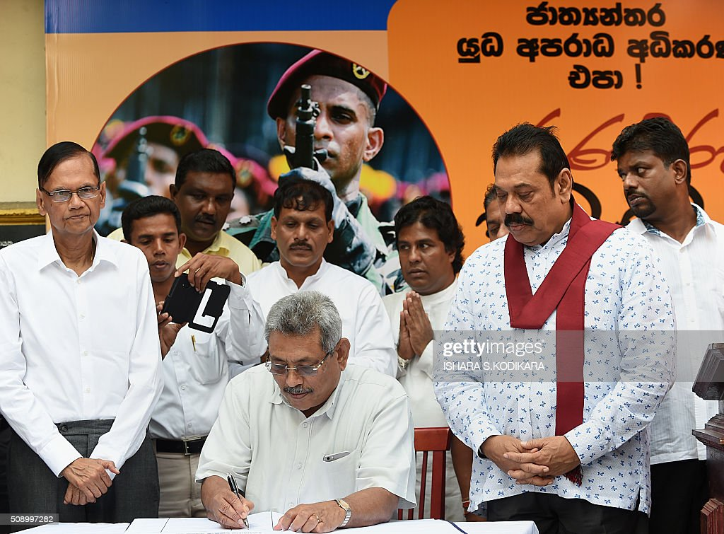 Gotabhaya Rajapakse (C), who was the country's defence secretary in 2009, signs a petition as his brother and former president, Mahinda Rajapakse (front R), looks on in Colombo on February 8, 2016 against a UN-mandated investigation into alleged war crimes during the final stages of the islands Tamil separatist war. Former president Mahinda Rajapakse and his brother on February 8 denounced a visit by UN human rights chief Zeid Ra'ad Al Hussein to Sri Lanka as a 'big joke' and renewed their opposition to a UN-mandated war crimes probe. AFP PHOTO/ Ishara S. KODIKARA / AFP / Ishara S.KODIKARA