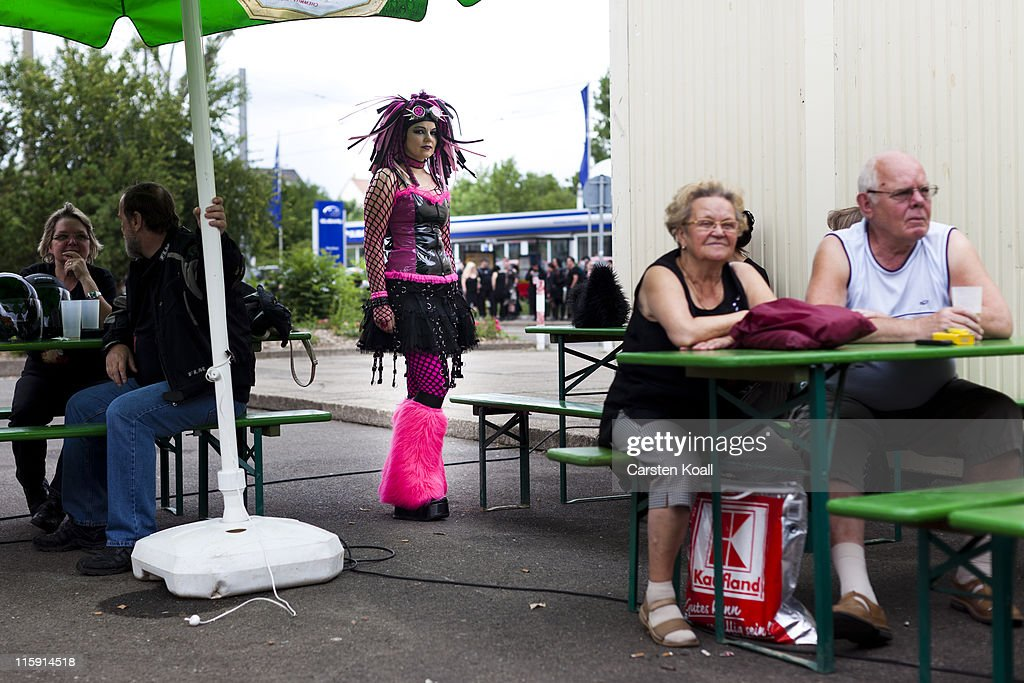 A gothic rock music enthusiast stays behind spectators during the annual Wave Gotik music festival on June 11, 2011 in Leipzig, Germany. The festival began in the 1990s and has since grown into one of the biggest gatherings of Goth scene followers in Europe with around 20,000 participants. Many of those attending wear elaborate outfits and make-up for which they require hours of painstaking preparation and that also show a departure from the traditional black of the Goth scene. Punk remains a strong influence in todays Goth style as witnessed in Leipzig, but newer trends, with names like Cybergoth and Steampunk, have emerged that blend bold colors, Victorian fashion elegance and 19th and 20th century factory accessories into a look reminiscent of a mutated Venetian carnival. The five-day festival includes performances by around 200 bands.