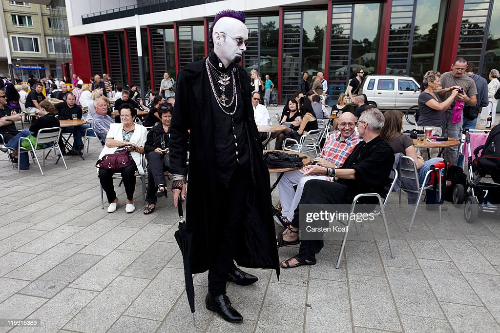 A Gothic rock music enthusiast walks on the street next to sitters during the annual Wave Gotik music festival on June 11, 2011 in Leipzig, Germany. The festival began in the 1990s and has since grown into one of the biggest gatherings of Goth scene followers in Europe with around 20,000 participants. Many of those attending wear elaborate outfits and make-up for which they require hours of painstaking preparation and that also show a departure from the traditional black of the Goth scene. Punk remains a strong influence in todays Goth style as witnessed in Leipzig, but newer trends, with names like Cybergoth and Steampunk, have emerged that blend bold colors, Victorian fashion elegance and 19th and 20th century factory accessories into a look reminiscent of a mutated Venetian carnival. The five-day festival includes performances by around 200 bands.