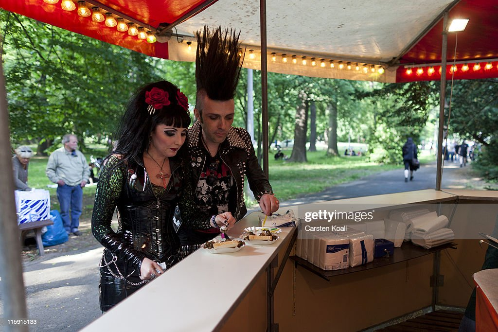 Gothic rock music enthusiasts eat a curry sausage at a snack stand during the annual Wave Gotik music festival on June 11, 2011 in Leipzig, Germany. The festival began in the 1990s and has since grown into one of the biggest gatherings of Goth scene followers in Europe with around 20,000 participants. Many of those attending wear elaborate outfits and make-up for which they require hours of painstaking preparation and that also show a departure from the traditional black of the Goth scene. Punk remains a strong influence in todays Goth style as witnessed in Leipzig, but newer trends, with names like Cybergoth and Steampunk, have emerged that blend bold colors, Victorian fashion elegance and 19th and 20th century factory accessories into a look reminiscent of a mutated Venetian carnival. The five-day festival includes performances by around 200 bands.