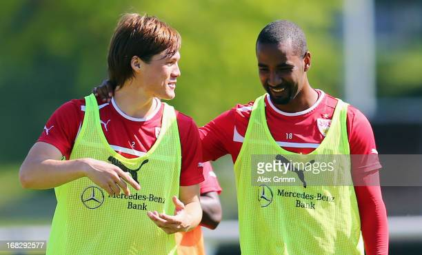 Gotoku Sakai chats with team mate Cacau during a VfB Stuttgart training session at the club's premises on May 8 2013 in Stuttgart Germany