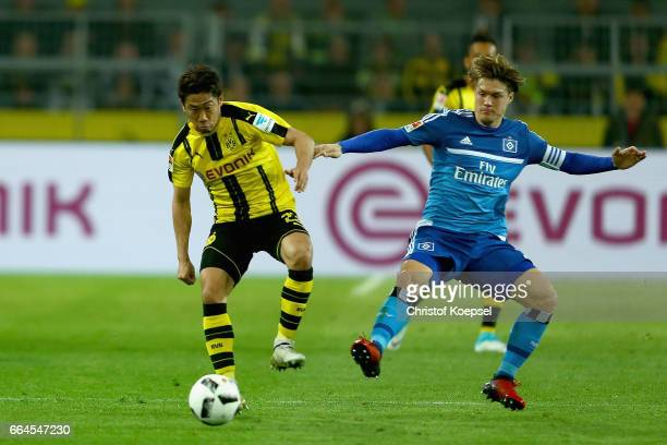 Gotoku Sakai of Hamburg challenges Shinji Kagawa of Dortmund during the Bundesliga match between Borussia Dortmund and Hamburger SV at Signal Iduna...