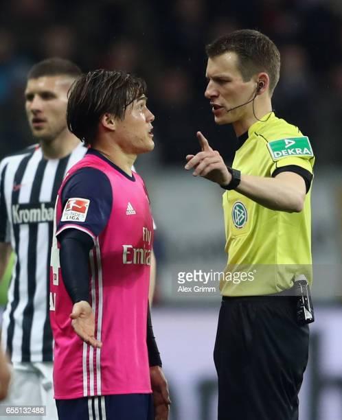 Gotoku Sakai of Hamburg discusses with referee Benjamin Cortus during the Bundesliga match between Eintracht Frankfurt and Hamburger SV at...