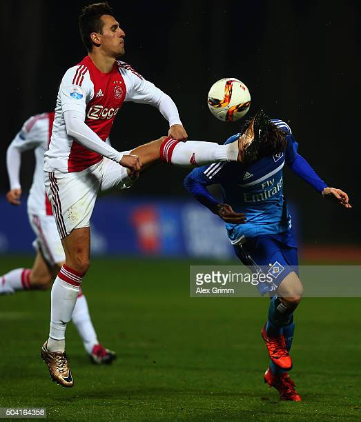 Gotoku Sakai of Hamburg is challenged by Arkadiusz Milik of Ajax during a friendly match between Hamburger SV and Ajax Amsterdam at Gloria Sports...