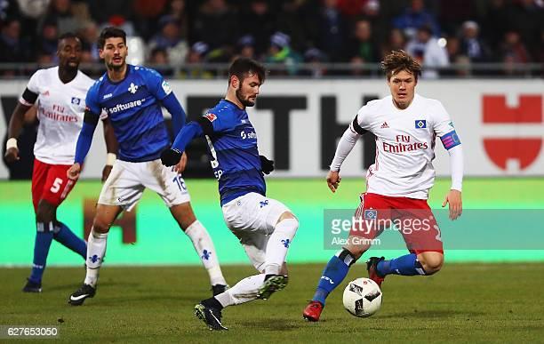 Gotoku Sakai of Hamburg is challenged by Marcel Heller of Darmstadt during the Bundesliga match between SV Darmstadt 98 and Hamburger SV at Stadion...