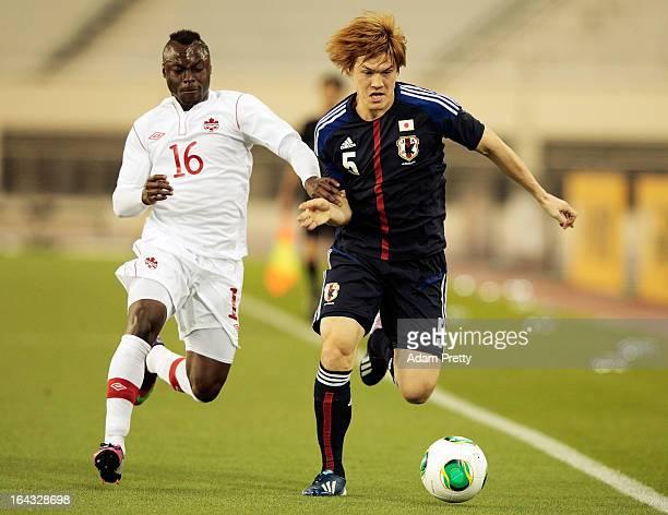 Gotoku Sakai of Japan is challenged by Randy EdwiniBonsu of Canada during the international friendly match between Japan and Canada at Khalifa...