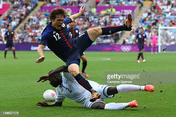 Gotoku Sakai of Japan is tackled by Wilmer Crisanto of Honduras during the Men's Football first round Group D Match between Japan and Honduras on Day...