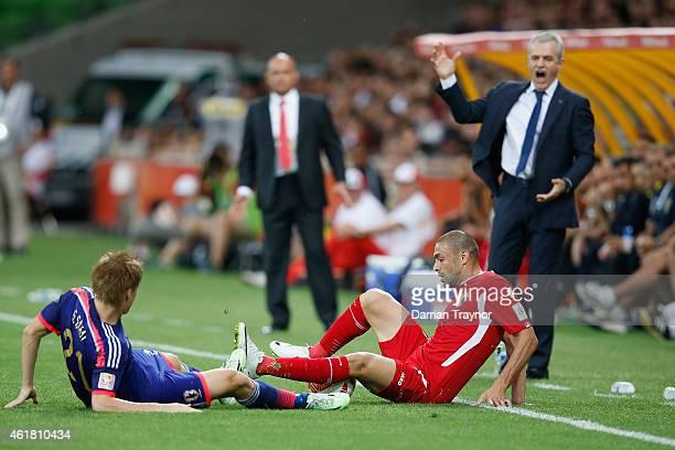 Gotoku Sakai of Japan is taken down by Odai Al Saify of Jordan as coach of Japan Javier Aguirre reacts during the 2015 Asian Cup match between Japan...