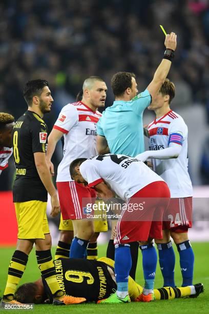 Gotoku Sakaiof Hamburg receives a yellow card by referee Felix Swayer during the Bundesliga match between Hamburger SV and Borussia Dortmund at...