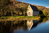 Autumnal mirror reflections of St. Finnbarr's oratory on Gougane Barra lake in West Cork.