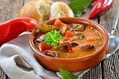Hot Hungarian goulash soup served in a ceramic bowl with a fresh roll
