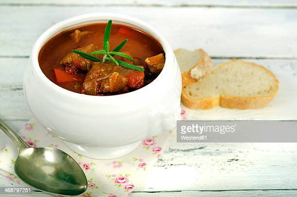 Goulash soup with bread on wooden table