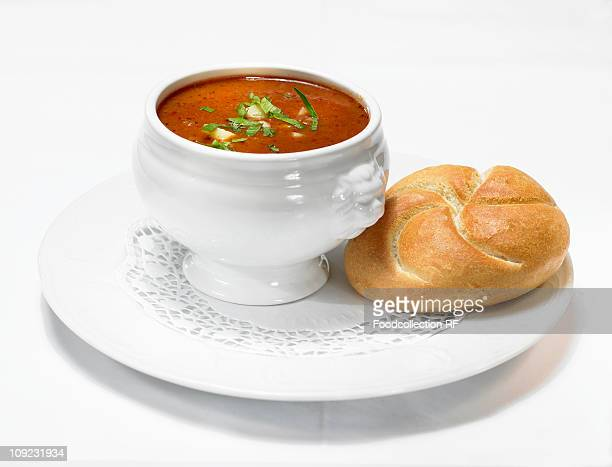 Goulash soup with bread roll on plate, close-up