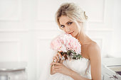 Classical young gourgeous bride. Studio interior fashion shot of fashion model in wedding dress with bouquet of flowers sitting in white room. Blonde woman portait with profeshional make-up and hairst