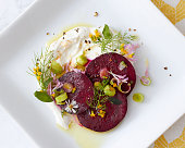 An artfully plated beet salad dish on a white square plate.