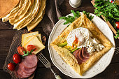Crepe galette with meat, avocado, soft white cheese and poached egg on white plate. Sliced yellow cheese, pastrami, cherry tomatoes, green salad and stack of crepes on side. Top view. Food gasing