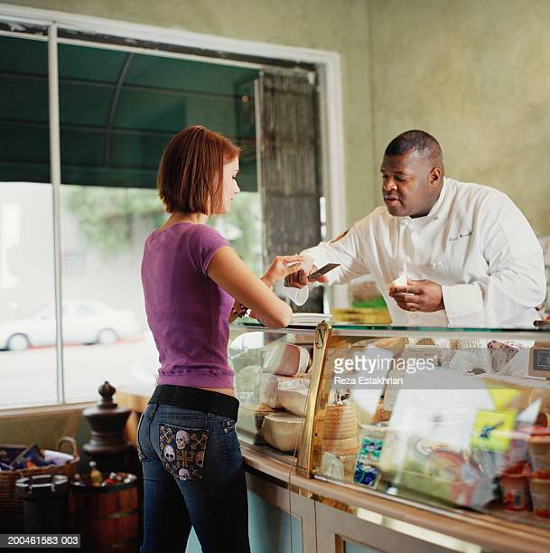 Gourmet shop owner offering cheese sample to female customer