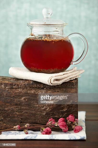 Gourmet-Teekanne mit rotem rooibos-Kräuter auf Holz-block
