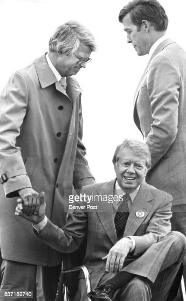 Gov Dick Lamm Reaches down to shake hands with president carter Handing at right at Solar Energy Research institute is Rep Tim Wirth whose district...