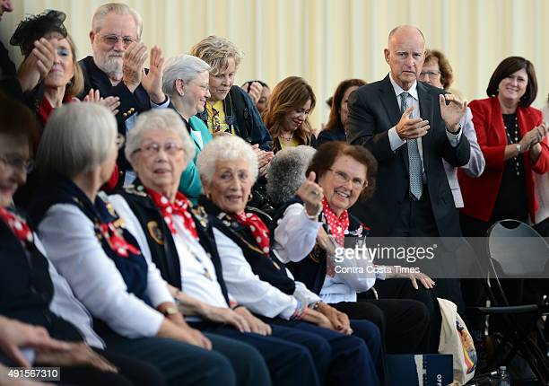 Gov Jerry Brown stands to applaud female factory workers from WWII as he visits the Rosie the Riveter National Monument to sign the equal pay act...