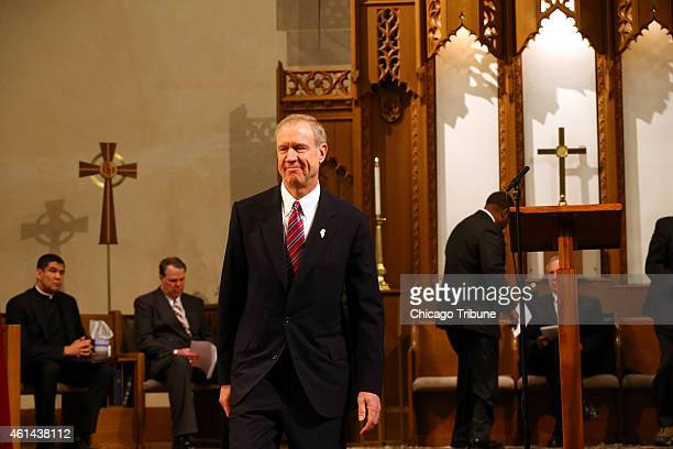 Govelect Bruce Rauner returns to his seat after praying with Rev James Meeks at an interfaith prayer service at First Presbyterian Church on Monday...