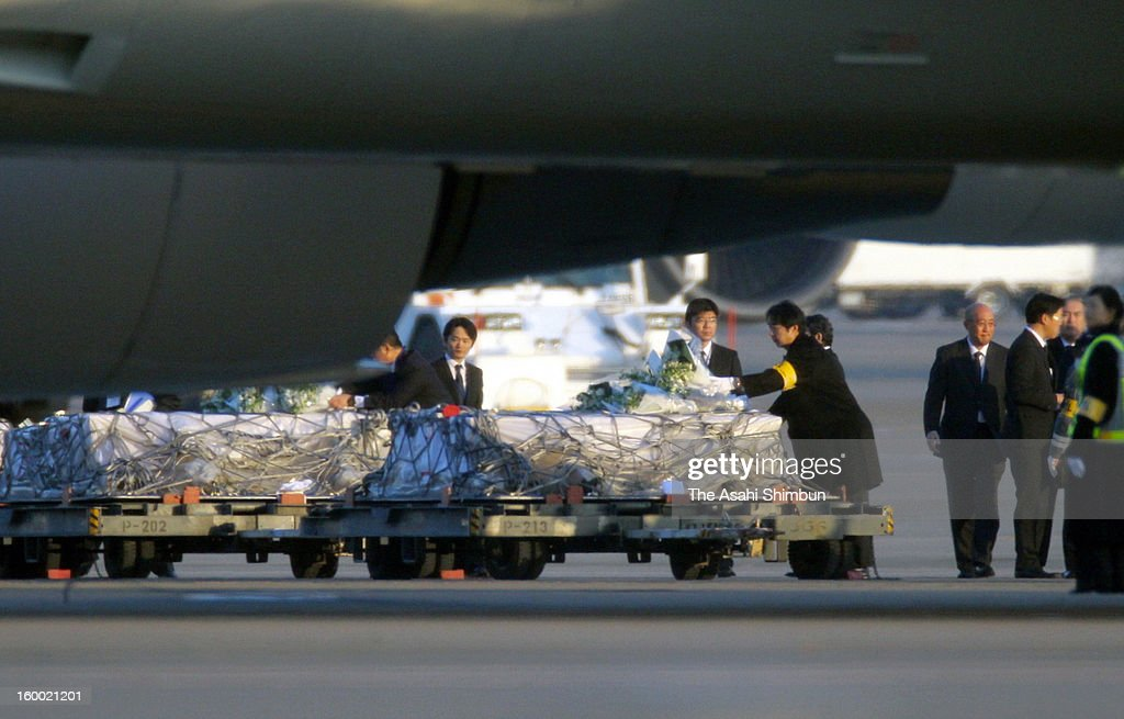 Goverment officials, Japanese plant constructor JGC staffs offer flower banches to the coffins of the victims killed in the Algerian hostage crisis at Tokyo International Airport on January 25, 2013 in Tokyo, Japan. A Japanese government aircraft lands at Tokyo International Airport on January 25, 2013 in Tokyo, Japan. The aircrafts carrys the seven survivors and the bodies of nine victims of the Algerian hostage crisis.