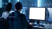 Government Agent is Working in Surveillance Control Center Full of Monitors and Servers. Possibly Government Agency Conducts Investigation. He Works With White Screen Isolated. Good for Template.