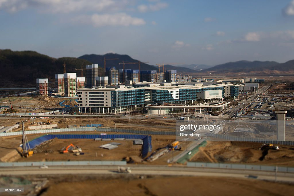 Government buildings, right, stand completed as other buildings stand under construction in this photograph taken with tilt-shift lens in Sejong, South Korea, on Tuesday, Dec. 4, 2012. The construction of Sejong City 120 kilometers (75 miles) south of the capital fulfills the vision of the late President Roh Moo Hyun, who pledged to reduce the dominance of Seoul and pump money into a region courted for its swing voters. Photographer: SeongJoon Cho/Bloomberg via Getty Images