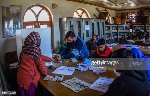 A government employee marks the finger of with the indelible ink of a Kashmiri Muslim woman before casting her vote during the elections of the lower...
