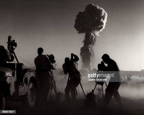 Government filmmakers document an atomic bomb explosion at the test site in Nevada 1957 A Jeep has been equipped with a movie camera and is not far...
