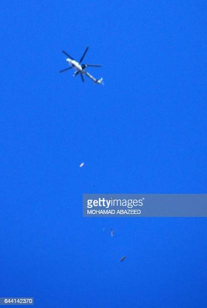 A government forces helicopter is reportedly seen dropping barrel bombs over the southern Syrian city of Daraa on February 23 2017 / AFP / MOHAMAD...
