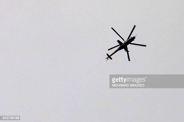 A government forces MI24 helicopter is seen from the southern Syrian city of Daraa on February 22 2017 / AFP / MOHAMAD ABAZEED