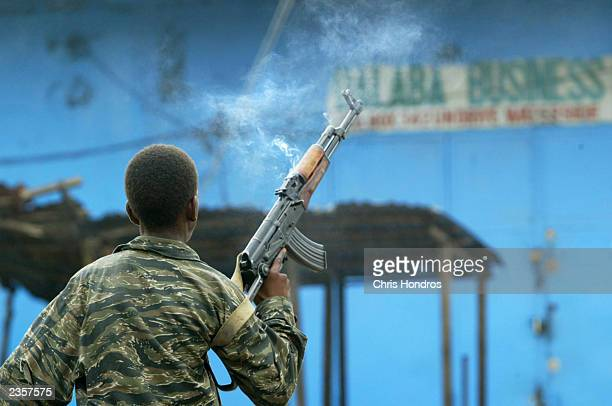 A government loyalist soldier fires his rifle into the air to motivate troops during fighting near front line positions August 2 2003 in Monrovia...