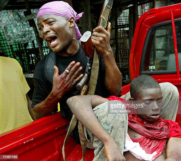 A government loyalist soldier grieves as a comrade dies of wounds suffered during a battle near front line positions August 2 2003 in Monrovia...