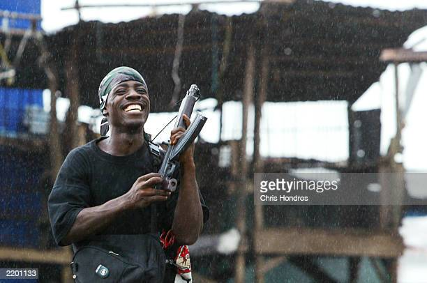A government militia soldier brandishes his weapon and smiles July 25 2003 at a key bridge in Monrovia Liberia The standoff at Monrovia's bridges...